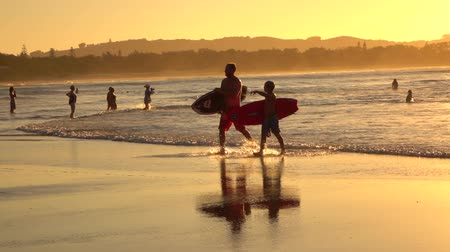 BYRON BAY, AUSTRALIA - 12th DECEMBER 2015: Surfers father and son coming out of ocean after surfing session, carrying surfboards and walking in shallow sea water at golden sunset in sunny summer Wideo