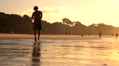 BYRON BAY, AUSTRALIA - 12th DECEMBER 2015: SLOW MOTION: Young people spending hot summer evenings at seaside, people chatting after surfing and jogging along the beautiful sandy beach at golden sunset