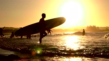 surfovat : SLOW MOTION: Unrecognizable people enjoying summer adventure, surfing and standing in shallow sea at beautiful golden sunset in surf town Byron. Young man with longboard in hands going into the water