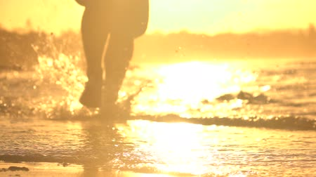 малая глубина резкости : SLOW MOTION CLOSE UP, DOF: Young sportsman jogging in shallow water on beautiful beach at amazing golden sunset. Active male athlete running in ocean surf and splashing water in hot summer evening.
