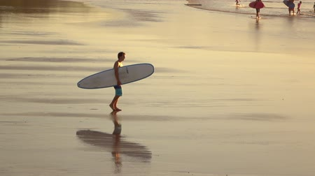 sekély : SLOW MOTION: Young surfer male sportsman with surfboard in his hands walking down beautiful wet sandy beach. Sea waves washing smooth sand on shore at amazing golden sunset in surfing town, Byron Bay Stock mozgókép