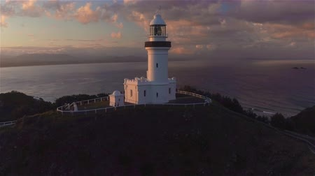 nowoczesne : AERIAL: Beautiful white lighthouse on the top of the hill above the calm ocean at golden sunset. Flying around new lighthouse at seaside in summer evening