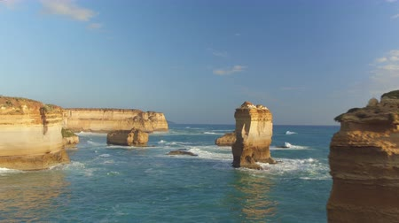 известняк : AERIAL CLOSE UP: Flying over the top of Twelve Apostles stack, revealing other limestone formations standing proudly in shallow sea along the rocky cliff coast at sunny Australian Great Ocean Road