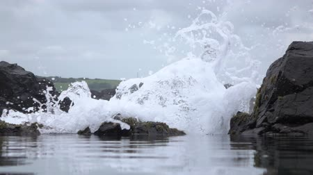 povstání : SLOW MOTION, LOW ANGLE, CLOSE UP: Ocean water wave crushing violently against rough shoreline wall, splashing and sprinkling high up. Beautiful meadow field on small hill and quarry in the background