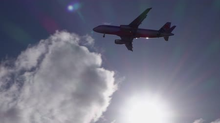 puffy cloud : GOLD COAST, AUSTRALIA - 14th DECEMBER 2015: Jetstar airplane flying its route and distancing in blue skies. Adventurous tourists traveling to discover new touristic places, departing from airport Stock Footage