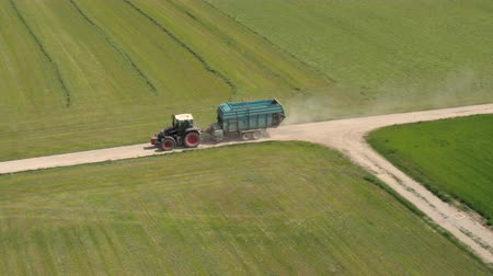 farm equipment : AERIAL: Agricultural tractor with loading trailer rising dust on dusty rural road leading through lush meadow, grass, clover fields on sunny spring day. Farmer driving through vast cultivated farmland Stock Footage