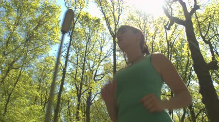 baixo ângulo vista : CLOSE UP, LOW ANGLE VIEW: Happy cheerful young woman runner jogging through big vast park on beautiful sunny spring day. Joyful athlete youthful girl running through tree avenue in stunning forest Stock Footage