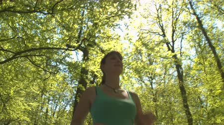 mladistvý : CLOSE UP, LOW ANGLE VIEW: Happy cheerful young woman runner jogging through big vast park on beautiful sunny spring day. Joyful athlete youthful girl running through tree avenue in stunning forest Dostupné videozáznamy
