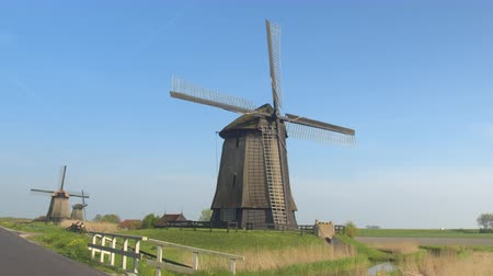 ülkeler : CLOSE UP: Stunning traditional wooden windmill in charming picturesque lowland countryside under blue cloudless sky. Beautiful big mill next to local road and small bridge across the river canal