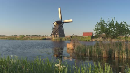 poblíž : Big wooden cradle floating on calm river near riverbank telling the folkloric tale about Kinderdijk. Beautiful traditional old windmill with blades turning on grassy plain farm field in the background