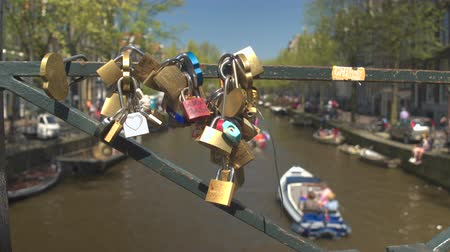 eternal : AMSTERDAM, NETHERLANDS - 7th MAY 2016: Padlocks locked as symbol of eternal friendship and love on beautiful old bridge. Boats in river canal riding tourists on sightseeing tours in sunny city centre Stock Footage