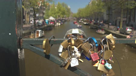 boat tour : AMSTERDAM, NETHERLANDS - 7th MAY 2016: Padlocks locked as symbol of eternal friendship and love on beautiful old bridge. Boats in river canal riding tourists on sightseeing tours in sunny city centre Stock Footage