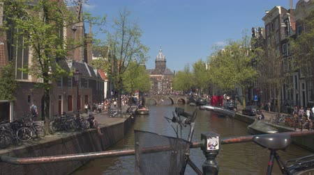 nizozemí : AMSTERDAM, NETHERLANDS - 7th MAY 2016: Crowded Amsterdam river canals on busy Saturday, people enjoying sunny afternoon hanging on riverbank, cruising the canals on boat ride tours and sightseeing