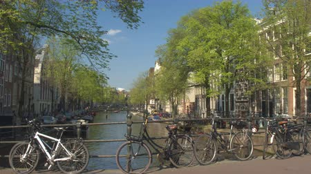 nizozemí : AMSTERDAM, NETHERLANDS - 7th MAY 2016: Antique bicycles locked on bridge, people enjoying sunny afternoon hanging on riverbank, relaxing and sightseeing. Small cruising boats anchored in river canals