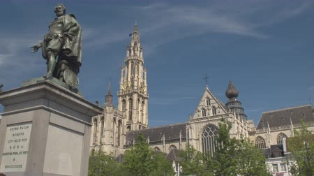 belga : CLOSE UP, LOW ANGLE VIEW: Baroque painter Petro Paulo Rubens statue on famous historic Groenplaats Green square in front of majestic Cathedral of Our Lady and tall belfry in sunny Antwerp, Belgium Stock Footage