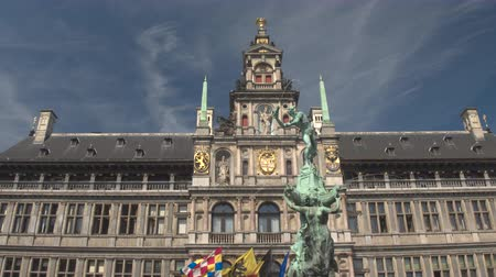 ornamentação : CLOSE UP, LOW ANGLE VIEW: Brabo statue fountain in front of stunning famous City Hall richly ornamented building, Antwerp, Belgium. Fascinating historic architecture on Great Market square in Antwerp