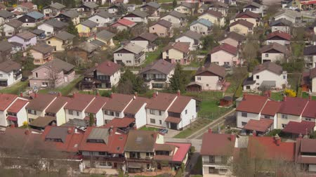sessiz : AERIAL: Flying above residential row houses in beautiful suburban town on a beautiful day in sunny spring. Cute modern homes in quiet suburbia. Stok Video