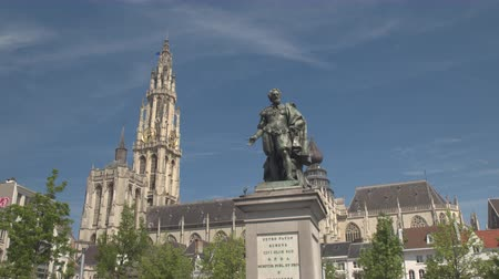 anıt : CLOSE UP, LOW ANGLE VIEW: Baroque painter Petro Paulo Rubens statue on famous historic Groenplaats Green square in front of majestic Cathedral of Our Lady and tall belfry in sunny Antwerp, Belgium Stok Video
