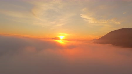 high rises : AERIAL: Beautiful golden sunset sun setting above the misty clouds Stock Footage