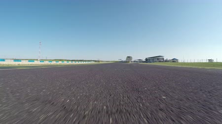 경마장 : Sarvar, Hungary, April 15, 2016,FPV LOW ANGLE VIEW: Racecar driving fast on the race track on professional racing circuit. Personal car driving the practice qualifying lap on trackday at the ring.