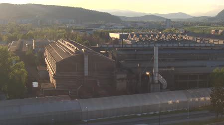 rundown : AERIAL: Flying around big industrial zone with old run down factory and modernized warehouse and manufacturing business buildings in front of the city. Abandoned heavy industry plant in sunny evening Stock Footage