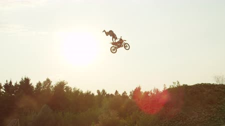 enduro : SLOW MOTION: Extreme pro motocross rider riding fmx motorbike, jumping huge jump performing dangerous stunt against the sky. Professional motocross biker jumps big air trick over sunset sun Stock Footage