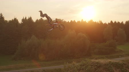 trik : AERIAL SLOW MOTION: Extreme pro motocross rider riding fmx motorbike, jumping big air kicker performing dangerous stunt. Professional motocross biker jumps  trick over golden sunset sun.