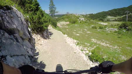 легкий : POV FIRST PERSON VIEW: Extreme biker riding downhill along the singletrack bandah rocky track and skinny wooden trails in mountain bike park. Beginner cyclist biking on the easy bikepark flow trail. Стоковые видеозаписи