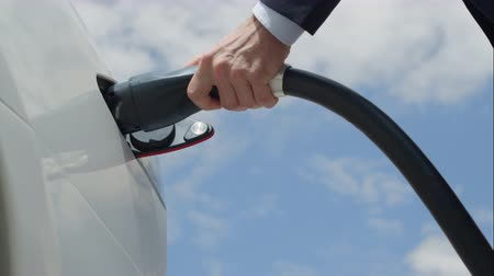 melez : SLOW MOTION CLOSE UP: Unrecognizable businessman plugging electric car at charging station. White electrical hybrid car recharging. Environmentally conscious man charging his electric vehicle.