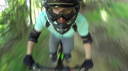 легкий : PORTRAIT CLOSE UP: Extreme biker riding downhill e-bike on singletrack bandah track and skinny wooden trails in mountain bike park. Beginner cyclist biking electric bicycle on easy bikepark flow trail Стоковые видеозаписи