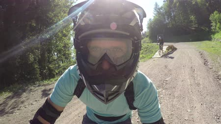 óculos de proteção : PORTRAIT CLOSE UP: Extreme biker riding downhill e-bike on singletrack bandah track and skinny wooden trails in mountain bike park. Beginner cyclist biking electric bicycle on easy bikepark flow trail Vídeos