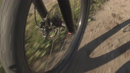 skalnatý : CLOSE UP: Offroad electric bicycle tire wheel spinning along the white gravel road through the meadow fields. Front tire of mountain e-bike spinning along the dirt trail through nature in sunny summer