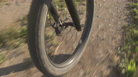 mtb : CLOSE UP: E-bike tire wheel spinning along the white gravel road through the meadow fields. Front tire of electric mountain bike spinning along the offroad trail through nature in sunny summer