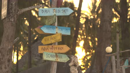 milestone : CLOSE UP: Beautiful wooden handmade sign plates on the shore in form of an arrow showing the distance to countries and cities with amazing lush tropical forest and golden sunset in the background