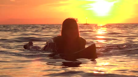 úmido : SLOW MOTION, CLOSE UP: Young happy woman paddling out on surf in deep ocean water at beautiful golden sunset. Girl relaxing on surfboard and enjoying her vacation on dreamy Zanzibar, Tanzania