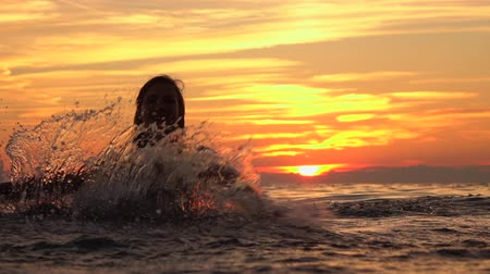 Танзания : SLOW MOTION, CLOSE UP: Young playful cheerful woman standing in shallow ocean and splashing sea water around. Happy female moving in circles and sprinkling ocean water at stunning golden sunset