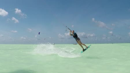 kitesurfer : SLOW MOTION CLOSE UP: Happy young female kiter kitesurfing and jumping rally on perfect turquoise sea on a sunny day. Extreme kiteboarder woman kiteboarding in beautiful blue lagoon in Zanzibar island