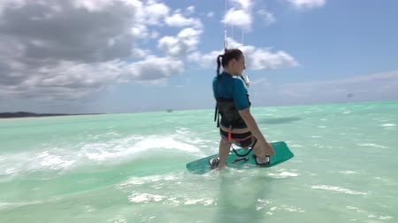 kitesurfer : SLOW MOTION: Young kiter girl kitesurfing in turquoise ocean with exotic sand beach in background on sunny day. Cheerful kiteboarder woman kiting in beautiful blue lagoon on vacation in Zanzibar Stock Footage