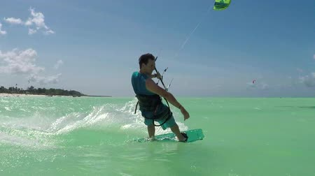kitesurfer : SLOW MOTION: Smiling young kiter kitesurfing showing surf shaka sign in blue ocean on sunny day. Cheerful kiteboarder man kiting in beautiful tropical sandy beach lagoon on fun summer vacation Stock Footage
