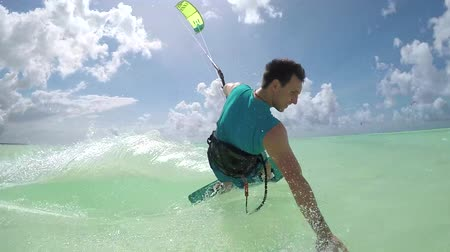 kitesurfer : SLOW MOTION: Smiling young kiter hand drag kitesurfing in turquoise ocean on sunny day. Cheerful kiteboarder man kiting in beautiful tropical sandy beach lagoon on summer vacation in Zanzibar island