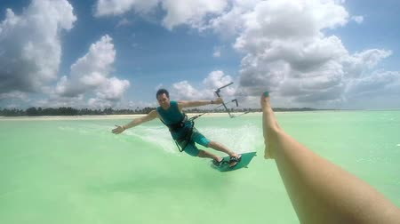 kitesurfer : SLOW MOTION: Smiling young kiter kitesurfing and high five slapping in turquoise ocean on sunny day. Cheerful kiteboarder man kiting in beautiful tropical sandy beach lagoon on summer vacation