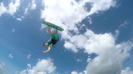 kitesurfer : SLOW MOTION: Happy smiling kite surfer jumping and showing shaka sign in turquoise ocean on sunny day. Extreme cheerful kiteboarder man kiting and jumping over camera in blue lagoon on summer vacation Stock Footage