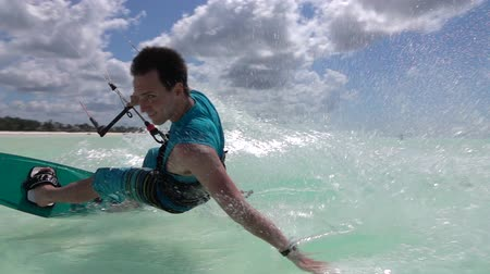 trascinare : SLOW MOTION: Smiling young kiter hand drag kitesurfing in turquoise ocean on sunny day. Cheerful kiteboarder man kiting in beautiful tropical sandy beach lagoon on summer vacation in Zanzibar island