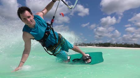 kitesurfer : SLOW MOTION: Young surfer kiteboarding and turning, splashing the water drops on beautiful blue ocean surface. Cheerful kiter man kitesurfing in amazing turquoise lagoon of exotic island Zanzibar Stock Footage