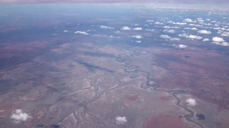 área de deserto : AERIAL: Flying high above endless vast hot dehydrated arid landscape of Great Victoria Desert and stunning meandering river watercourse curving back and forth across the dry red soil plains