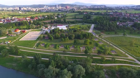 subúrbio : AERIAL: Flying above wide river running by big beautiful park with recreational footpaths for long walks and jogging, barbecue area, green equestrian pasture fields and outdoors riding arenas