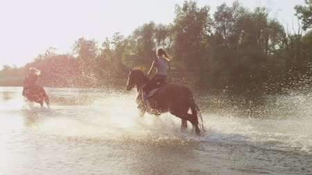 beregening : SLOW MOTION, CLOSE UP, DOF: Three cheerful girlfriends horseback riding along big, wide river on magical golden light summer day. Happy horses playing, splashing waterdrops as trotting in shallow water