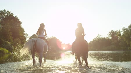 waterdrop : SLOW MOTION, CLOSE UP: Two cheerful girlfriends horseback riding in wide river on magical golden light sunny summer day. Happy horses splashing waterdrops when walking in shallow water Stock Footage