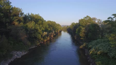 zarostlý : AERIAL: Flying above quiet river surface, lush riverside flowering bushes, tall trees and rocky riverbank. Small suburban town and highway in the distance with lush overgrown hills in the background Dostupné videozáznamy