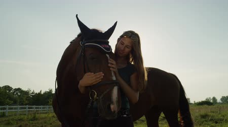 kleštěnec : SLOW MOTION, CLOSE UP: Beautiful smiling young female rider caressing and petting her beloved dark brown horse on stunning sunny summer day. Loving friendship between pretty mare and cheerful girl Dostupné videozáznamy